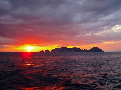 Bootscharter Rom – Neapel: Die Sonne versinkt hinter der kleinen Insel Palmarola im Meer